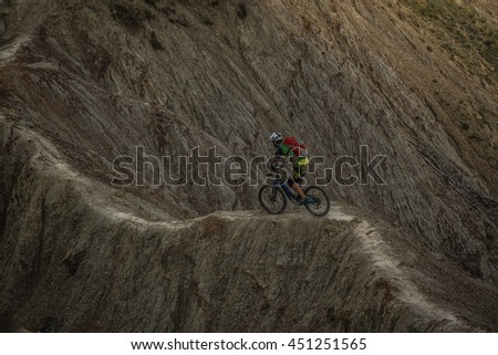 A man going downhill oh his mountain bike on trail - stock photo