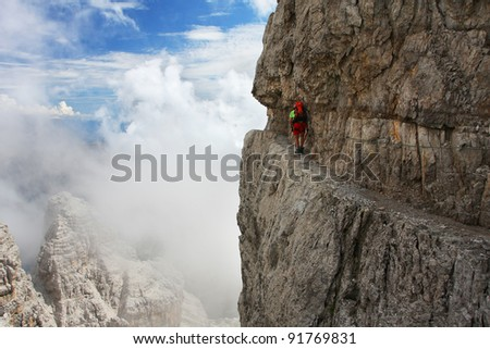 A man going through the difficult part of ferrata - Dolomiti mountains, Dolomiti di Brenta, Italy - stock photo