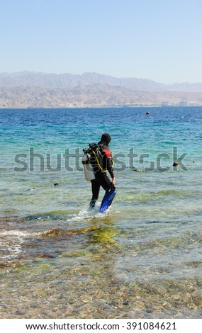 A man going to dive (Eialt, Israel). Coral Beach Nature Reserve in Eilat, one of the most beautiful coral reef in the world, is famous tourist and diver attraction. - stock photo