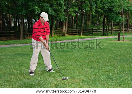A man golfing on a golf course wearing nice golfing attire. - stock photo