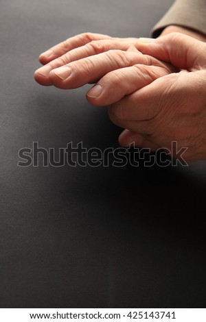 A man grips his aching hand on a dark background with copy space.