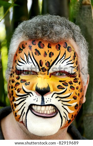 A man growling with a painted face. - stock photo