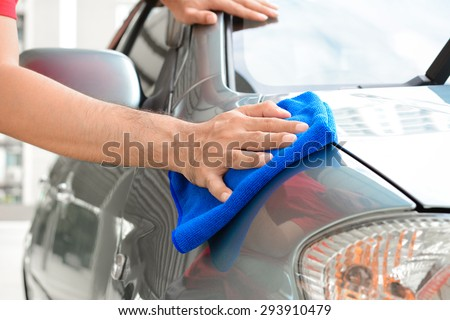 A man hand cleaning car with microfiber cloth - stock photo