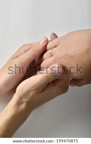 A man hand is held by two woman's hands with a marriage ring