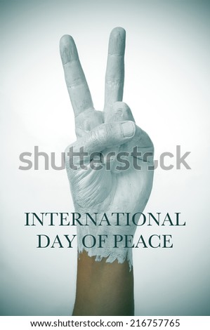 a man hand painted in white giving the V sign, as symbol of peace, and the sentence international day of peace - stock photo