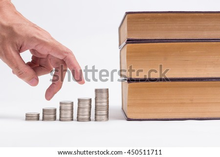 A man hand running up on coins to the books, invest in education of diploma and university student loan for study and money savings concept. - stock photo