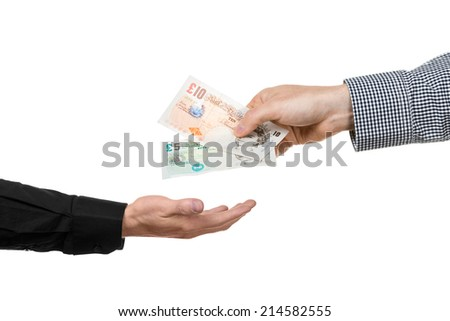 A man hands over British pound banknotes to another hand. - stock photo