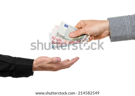 A man hands over euro banknotes to another hand. - stock photo
