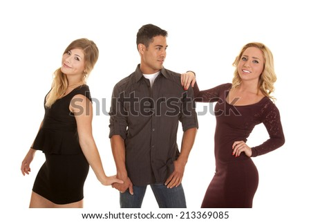 A man hanging on to two women, the women have smiles on their faces. - stock photo