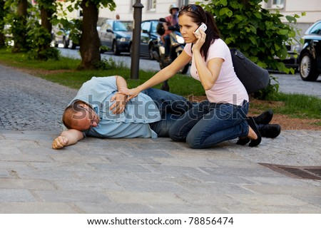 A man has a dizzy spell or a heart attack. Woman comes to the rescue. - stock photo