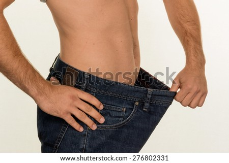 a man has taken off with a successful diet a lot of body weight. - stock photo