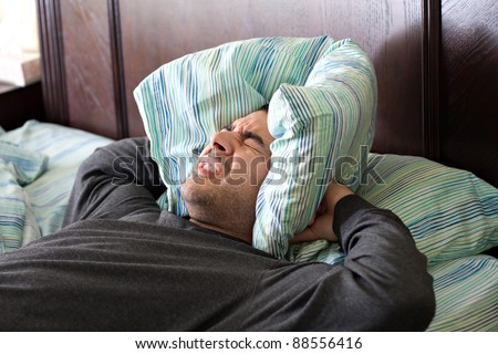 A man having trouble sleeping squeezes a pillow around his ears for some peace and quiet. - stock photo