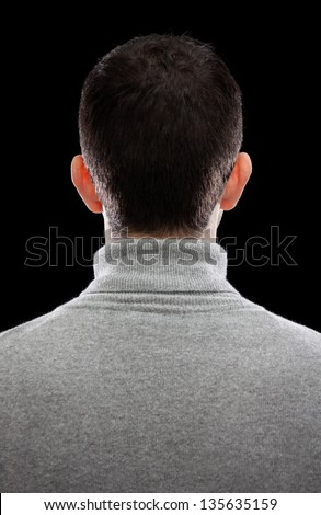 A man (head and upper torso) seen from behind, against a black background. His face remains unknown - only the ears, hair and back of his shoulders are visible. - stock photo