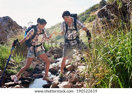 A man helping his girlfriend along the nature path that they are hiking - stock photo