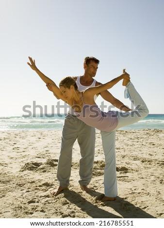 A man helping woman perform yoga on a beach. - stock photo