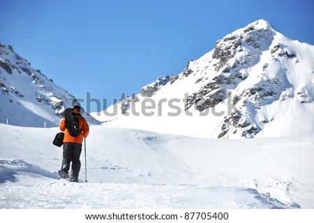 A man hiking in snowshoes along the mountain track