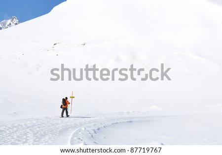 A man hiking in snowshoes along the mountain track - stock photo