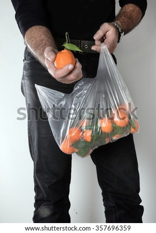 a man hold a plastic bag with tangerines - stock photo