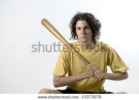 A man holding a  baseball bat and sitting on the floor with a serious look on his face. Horizontally framed photograph - stock photo