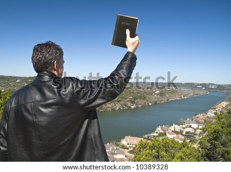 A man holding a bible in his raised hand, looking down over an affluent neighborhood. - stock photo