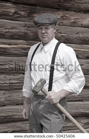A man holding a big sledge hammer by a log cabin
