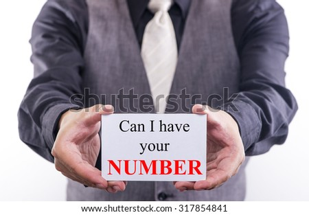 A Man holding a business card with the words, can I have your number, written on it. - stock photo