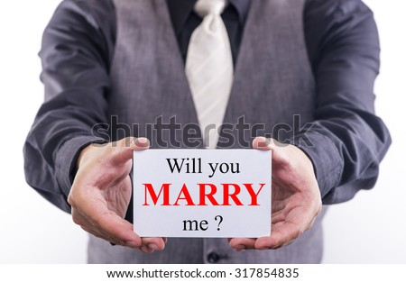 A Man holding a business card with the words, Will you marry me, written on it. - stock photo