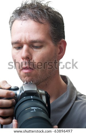 A man holding a camera with a black telephoto lens, making adjustments to it, isolated on white.