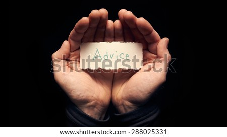 A man holding a card in cupped hands with a hand written message on it, Advice. - stock photo