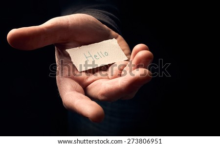 A man holding a card with a hand written message on it, Hello. - stock photo