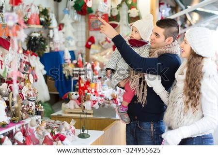 A man holding a child with his wife are standing at a counter at a christmas fair and pointing at christmas decorations. - stock photo