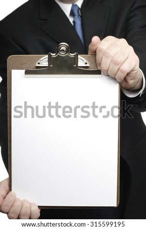 A man holding a clipboard with a white paper pad to camera. He is dressed in a jacket and tie.
