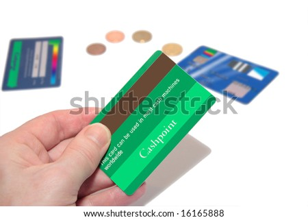 a man holding a credit card (made up fake card ) with more fake cards and coins in the background, to make a payment