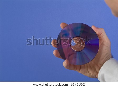 A man holding a DVD or CD with his face reflecting back at him with available copy space. - stock photo