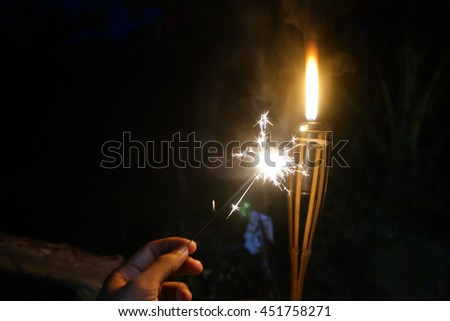 A man holding a firecracker, slightly soft focus and noise slightly appear due to high ISO