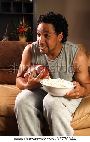 A man holding a football and popcorn on the edge of his seat