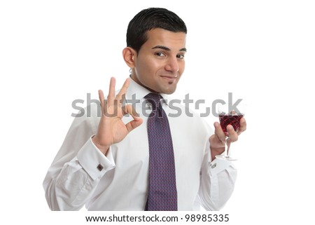 A man holding a glass of wine makes a hand sign to show approval, or excellence.  White background. - stock photo
