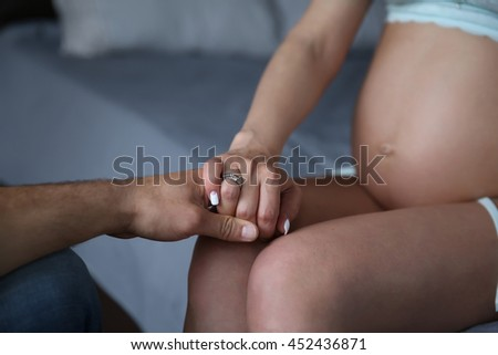 A man holding a hand of pregnant women on the background of her belly - stock photo