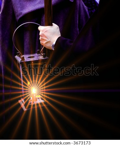 a man holding a lamp in the evening - stock photo