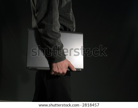 A man holding a notebook under his arm and leaving