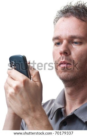 A man holding a PDA / Cel phone, looking at the screen while tapping on its screen, isolated on white.