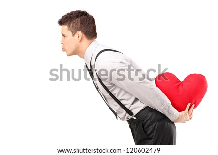 A man holding a red heart shape object and giving kisses isolated on white background - stock photo