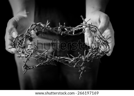 A Man holding a representation of the crown of thorns. - stock photo