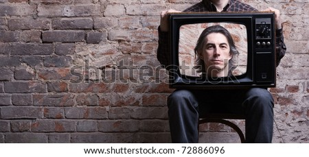 A man holding a retro television set sitting on a background of brick wall - stock photo