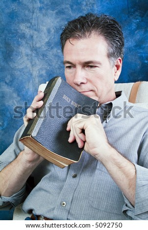 A man holding an old bible, with an expression of contemplation on his face. - stock photo