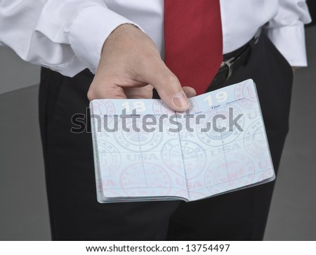 A man holding an open American passport. - stock photo