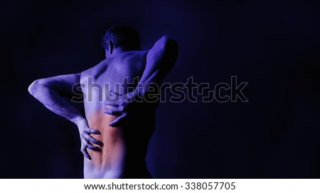 A man holding his back in pain. Studio shot with red marking the area of pain. - stock photo