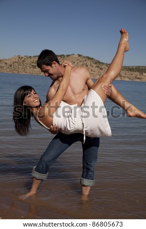 A man holding his girl up in the air dipping her while he stands in the water. - stock photo