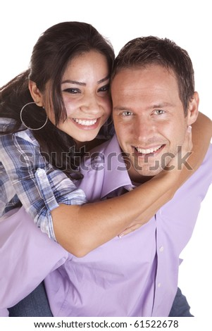 A man holding his girlfriend on his back carring her around and laughing. - stock photo