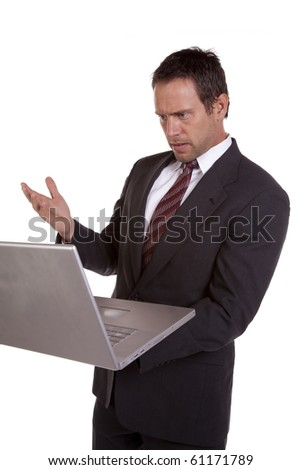 A man holding his laptop and looks surprised. - stock photo